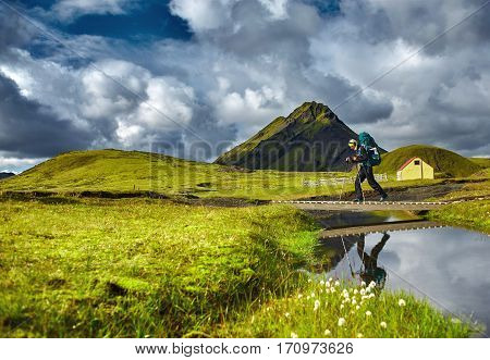 Travel to Iceland. Beautiful Icelandic landscape with hiker passes through creek, mountains, sky and clouds. Trekking in national park Landmannalaugar