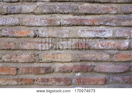 Old wall made of bricks with cement. reddish brick