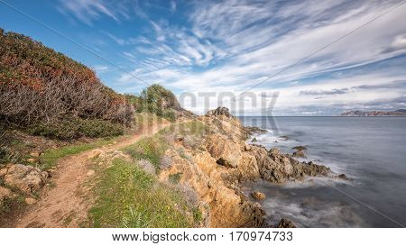 Slow shutter image of coastal footpath on rocky headland near Lozari beach in the Balagne region of Corsica with the Desert des Agriates in the distance