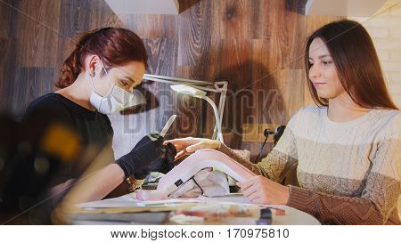 Manicurist in medical mask doing manicure for attractive woman in beauty salon, horizontal