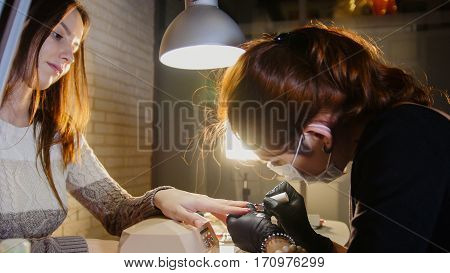 Professional beauty salon - manicure master doing cosmetic procedure for attractive young woman, telephoto