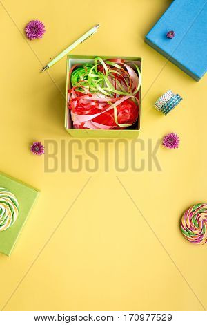 wrapping gifts in box for holiday top view mock up on yellow background