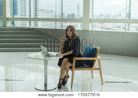Beautiful Young Asian business women using a laptop computer sitting on the chair with happiness and thinking with coffee on a table and city view background.