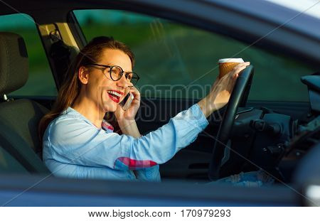 Young businesswoman speaks on the smartphone and drinking coffee while driving a car
