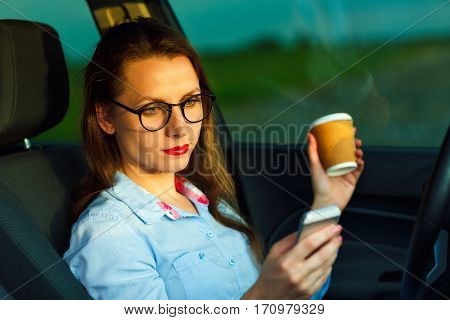 Young businesswoman sending a text message and drinking coffee while driving a car