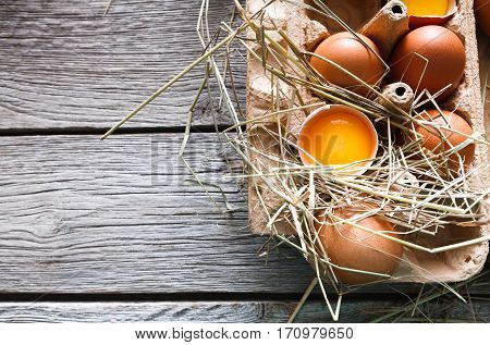 Fresh chicken eggs background. Brown and white eggs in craft carton pack on hay at rustic wood table. Top view with copy space. Rural still life, natural healthy food and organic farming concept.