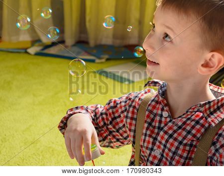 a child inflates soap bubbles and smiling