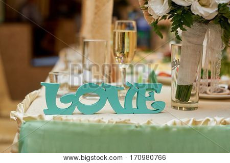 wooden letters love on wedding table bride and groom. poster