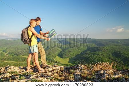 Two tourists on mountain read the map. Mens on top of cliff.