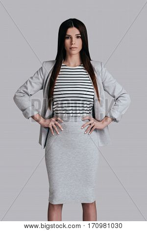 Modern woman. Gorgeous young woman in smart casual wear keeping hands on hip and looking at camera while standing against grey background