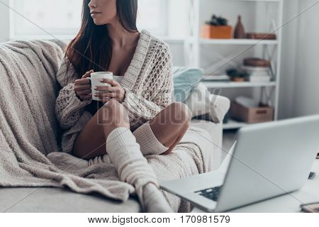 Enjoying morning coffee. Close-up of beautiful young woman holding cup while relaxing on couch at home