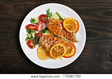 Cooked chicken breast with orange sauce and vegetable salad on wooden background top view