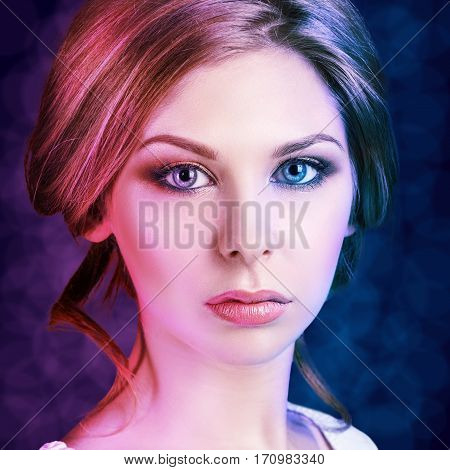 Glamour young woman with beautiful makeup over blue and purple background.