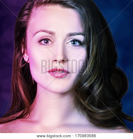 Beautiful woman with fresh daily makeup over purple and blue background.