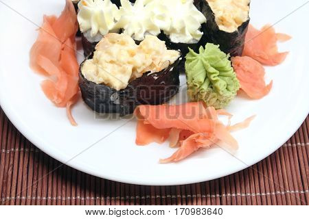 Sushi pieces on white plate on brown wicker straw mat top view closeup