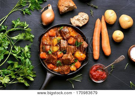 Stewed beef with potatoes and carrots in cast iron pan on dark background top view