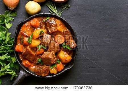 Beef stew with potatoes carrots and herbs on black background with copy space top view