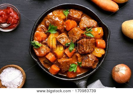 Beef meat stewed with potatoes and carrots in cast iron pan on dark background top view