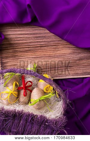 Easter Egg Decorative In Twine In Purple Basket On Wooden Table On Purple Background. Copy Space.