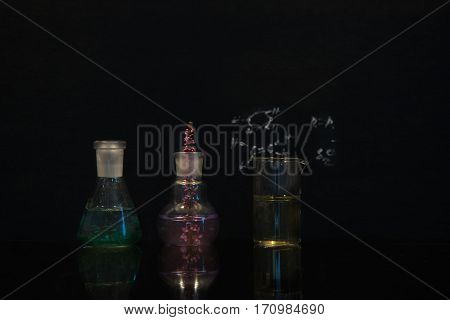 flask beaker with pink and green solution with flower in science lab on black background