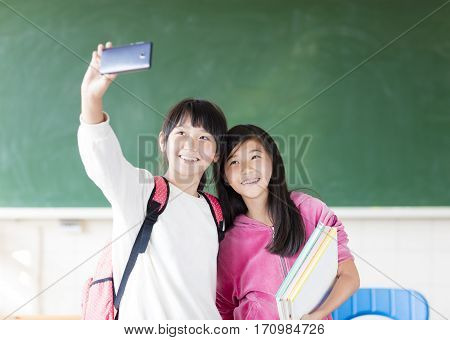 Two teenage girls student make selfie on the phone.