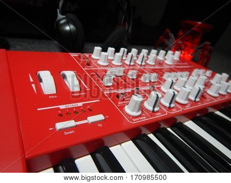 Red Synthesizer with reflection on black background