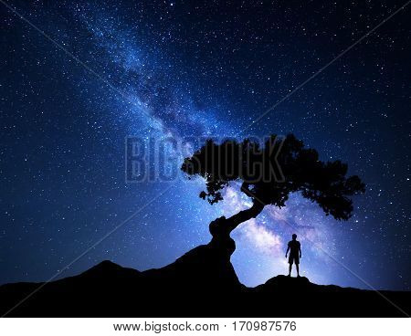 Milky Way. Night sky with stars old tree and silhouette of a standing alone man on the mountain. Blue milky way with light and man. Travel background. Silhouette of a man under the tree. Universe