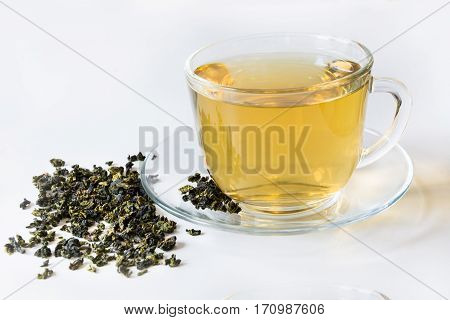 Glass cup with green tea and dry leaves of green tea on white background.