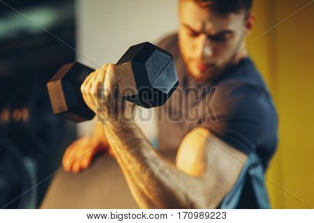 Handsome man doing biceps lifting with dumbbell on bench in a gym