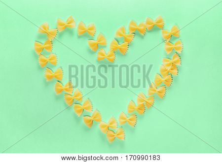 Heart Frame from Wwheat Pasta Farfalle on Green Background. Valentine's Day or Mother's Day.
