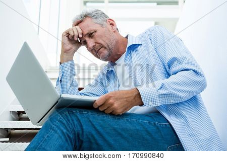 Tensed mature man using digital tablet on steps at home