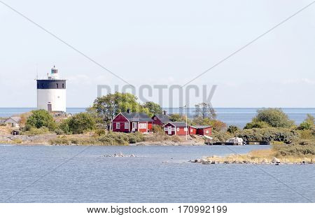 Lighthouse and some small red cottages on a tiny island in the swedish archipelago