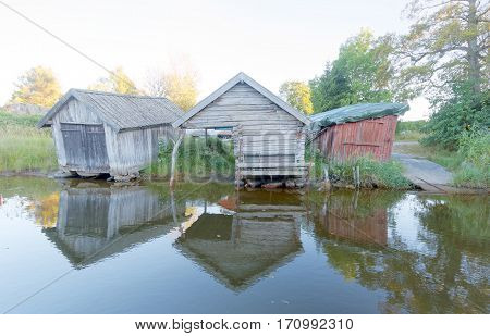 Old boathouse made of gray timber and planks reflecting in the water in the swedish archipelago