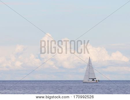 Sailboat on the glittering blue sea and large clouds a summar day