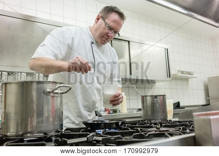 Chef preparing pancake dessert pouring dough into pan in kitchen