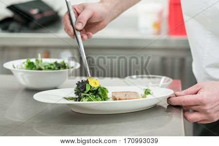 Chef cook finishing salad and pastry dish with pincers and flowers