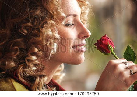 Young blonde woman smelling rose. Close up.