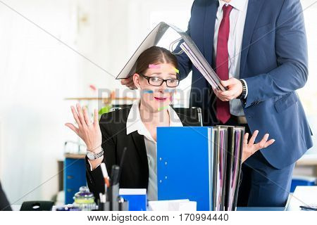 Desperate and stressed assistant covers her face with sticky notes while her colleague holds a ring binder above her head