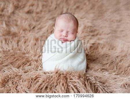 Adorable child in a white hat, wrapped with white blanket, sleeping tightly on furry surface