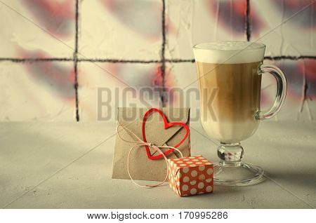 Coffee Latte with gift boxes, envelope and paper hearts. Pink, red, white colors on bright background. Love, Valentine's day concept. Copy space, horizontal, toned