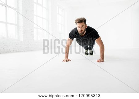 Handsome man in the black sportswear making pushups indoors in the white gym interior
