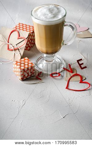Coffee Latte with gift boxes, envelope and paper hearts. Pink, red, white colors on bright background. Love, Valentine's day concept. Copy space, vertical