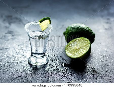 Silver tequila shot with fresh lime slices and salt on dark background