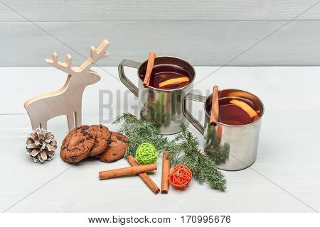 chocolate cookies with hot drink of mulled wine or tea with cinnamon spice stick in metallic mug near decorative wood deer and straw balls at christmas on grey wooden background