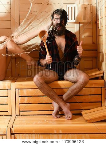Excited man or bearded hipster in red checkered shirt and sexy female legs wet with big splash of water. Male bather gives thumbs up gesture with spoon in sauna thermal bath on wooden background