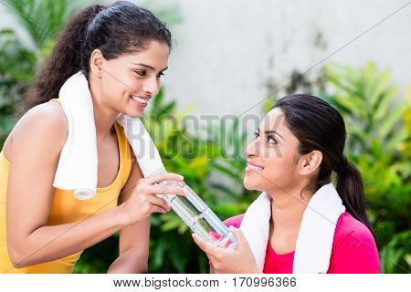 Cheerful young woman giving a bottle of natural plain water to her friend during workout session