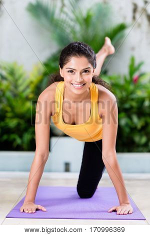 Young woman doing stretching exercise while sitting on yoga mat indoors