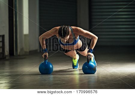 Young stron woman is doing push-ups by kettle bell.