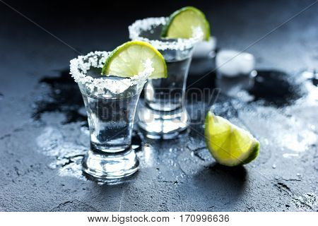 Silver tequila shot with fresh lime slices ice and salt on dark background