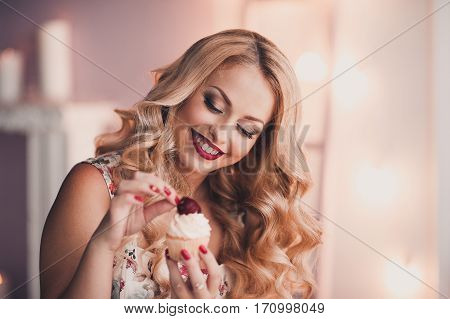Smiling girl holding cupcake with fresh strawberry on top. Sweet dessert. 20s.